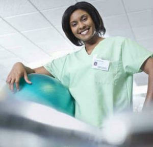 Recent female physical therapist assistant (PTA) grad posing for photo in PT clinic.