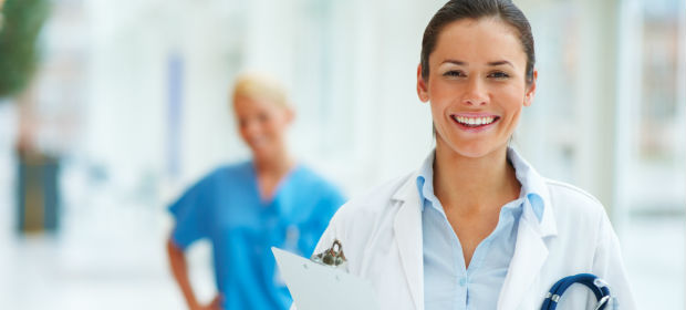 Female physician assistant student standing in foreground of photo taken at her school.