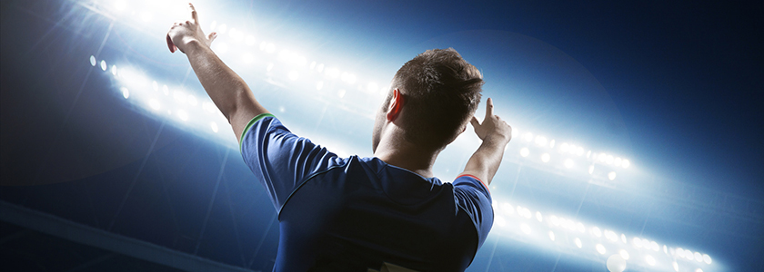World famous soccer player during night game pointing to his sports marketing team in the stands.